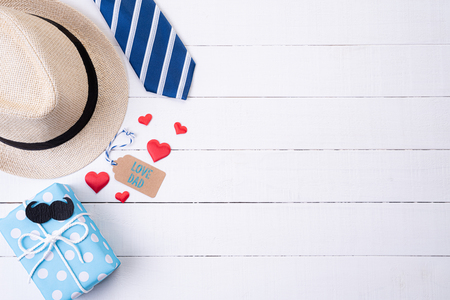 Happy fathers day concept. Top view of blue tie, beautiful gift box, man hat with glasses and retro film camera on white wooden table background. Flat lay.