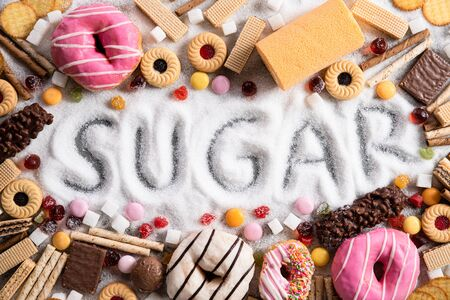Food containing sugar. mix of sweet donuts, cakes and candy with sugar spread and written text in unhealthy nutrition, chocolate abuse and addiction concept, body and dental care.