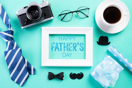 Happy fathers day concept. Top view of blue tie, beautiful gift box, black coffee cup, white picture frame with Happy fathers day text and retro film camera on bright green pastel background. Flat lay.