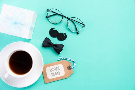 Happy fathers day concept. Top view of blue tie, beautiful gift box, coffee mug, glasses with LOVE DAD text on bright green pastel background.