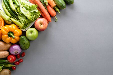 Healthy lifestyle and food concept. Top view of fresh vegetables, fruit, herbs and spices with a empty pink pastel plate on gray background.