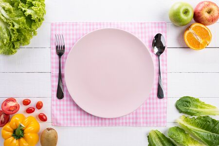 Healthy lifestyle and food concept. Top view of fresh vegetables, fruit, herbs and spices with a empty pink pastel plate on white wooden background.