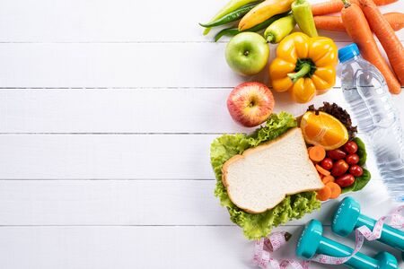 Healthy lifestyle, food and sport concept. Top view of athletes equipment Weight Scale measuring tape blue dumbbell, sport water bottles, fruit and vegetables on white wooden background.