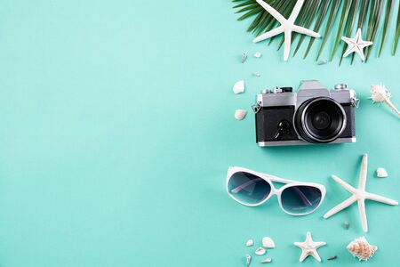 Beach accessories retro film camera, sunglasses, flip flop starfish beach hat and sea shell on green pastel background for summer holiday and vacation concept. Фото со стока