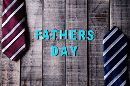 Happy fathers day concept. Top view of blue and red ties on dark wooden table background. Flat lay. Фото со стока