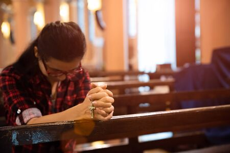Young woman sits on a bench in the church and prays to God. Hands folded in prayer concept for faith. Stok Fotoğraf