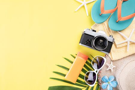 Beach accessories retro film camera, sunglasses, flip flop starfish beach hat and sea shell on yellow pastel background for summer holiday and vacation concept.