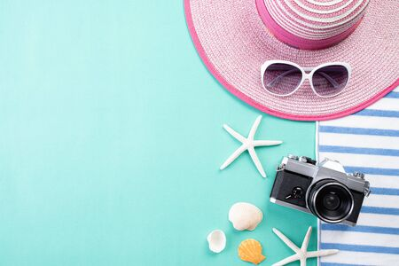 Beach accessories retro film camera, sunglasses, flip flop starfish beach hat and sea shell on green pastel background for summer holiday and vacation concept. Stok Fotoğraf