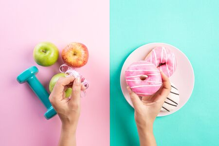 Healthy lifestyle, food and sport concept. Top view of Woman hand holding donut and measuring tape with athletes equipment dumbbell, green red apple on pink blue pastel background.
