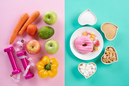 Healthy lifestyle, food and sport concept. Top view of healthy versus unhealthy. Donut and various types of sugar VS fruit vegetables, measuring tape and dumbbell on pink blue pastel background. Stock Photo