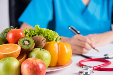 Healthy lifestyle, food and nutrition concept. Close up of fresh vegetables and fruits with stethoscope lying on doctor's desk. Stock Photo