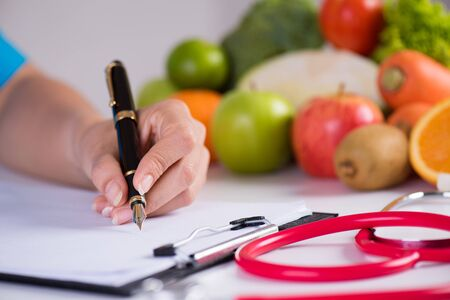 Healthy lifestyle, food and nutrition concept. Close up doctor woman hand holding pen to checklist with fresh vegetables and fruits with stethoscope lying on desk in background.