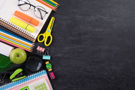 Education or back to school Concept. Top view of Colorful school supplies with books, color pencils, calculator, pen cutter clips and green apple on chalkboard background. Flat lay. Reklamní fotografie