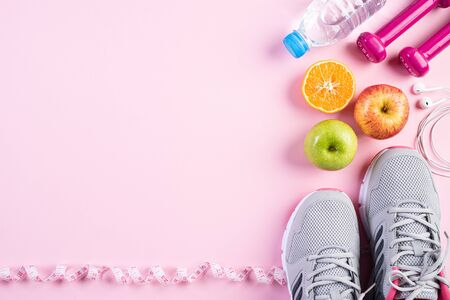 Healthy lifestyle, food and sport concept. Top view of athletes equipment measuring tape pink dumbbell, sport water bottles, sport shoes and green apple on pink pastel background.