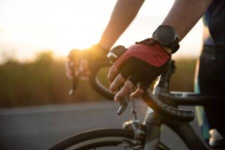 Hände in Handschuhen, die Rennradlenker halten. Konzept für Sport und Outdoor-Aktivitäten.
