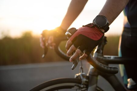 Hands in gloves holding road bicycle handlebar. Sports and outdoor activities concept.