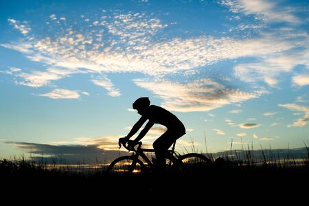 Silhouette of cyclist riding a road bike on open road in evening during sunset. Sports and outdoor activities concept. 写真素材 - 128806759