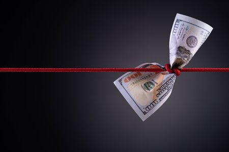 American dollar tied up in red rope knot on dark background with copy space. business finances, savings and bankruptcy concept. Stock fotó