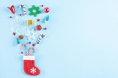 Christmas background concept. Top view of red sock splash out Christmas decoration with gift box candy cane, pine cones, red berries and bell on blue pastel background.