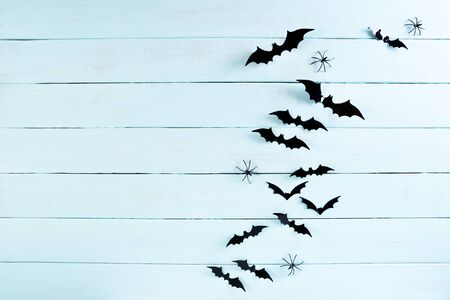Top view of Halloween crafts, black paper bats flying over blue pastel wooden background with copy space for text. halloween concept.