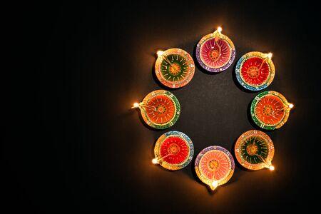 Happy Diwali - Lampade Clay Diya accese durante Dipavali, festa indù della celebrazione delle luci. Colorata lampada a olio tradizionale diya su sfondo bianco