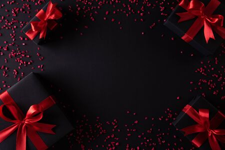 Top view of black christmas boxes with red ribbon on black background with copy space for text. black Friday composition.