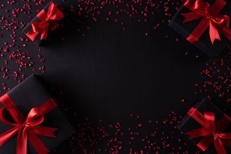 Vista superior de cajas de Navidad negras con cinta roja sobre fondo negro con espacio para copiar texto. composición del viernes negro. Foto de archivo