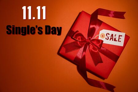 Online shopping of China, 11.11 single's day sale concept. Top view of christmas boxes with red ribbon on orange background with copy space for text  11.11 single's day sale. Stock Photo