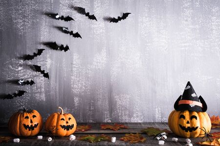 Orange ghost pumpkins with witch hat on gray wooden board background with bat. halloween concept. Reklamní fotografie