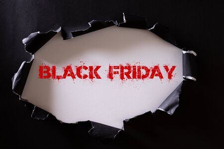 Top view of Black torn paper and the text black friday on a white background. Black Friday composition. Stock fotó