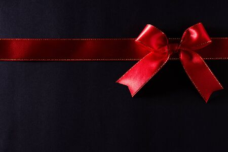 Top view of red ribbon on black background with copy space for text. black Friday and Boxing Day composition.
