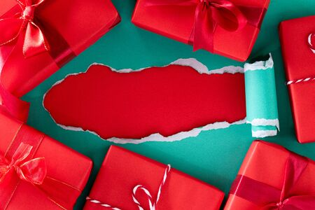 Boxing day Sale Online shopping. Top view of green pastel torn paper with red gift boxes. Stock Photo