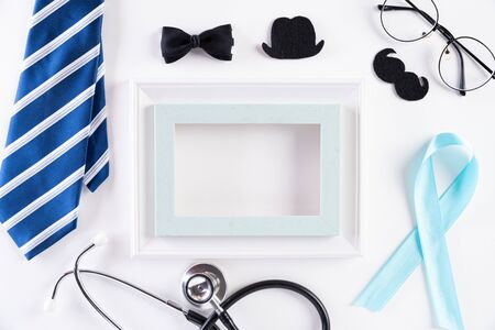 Blue ribbon with tie and stethoscope on white background representing an annual event during the month of November to raise awareness of mens health issues and prostate cancer with copy space.