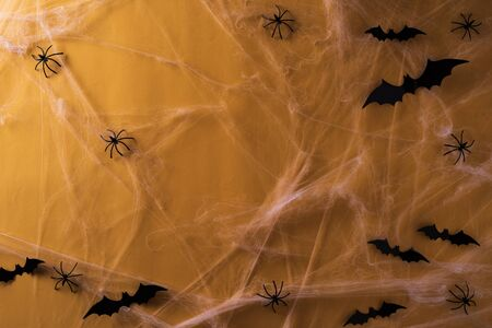 Top view of Halloween crafts, white Spider web with ghost, bat and spider on orange background with copy space for text. halloween concept.