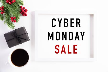 Top view of Cyber Monday Sale text on white picture frame with coffee cup, gift box and Christmas tree decoration, red berries on white background. Shopping concept and Cyber Monday composition.