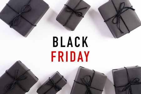 Top view of Black Friday Sale text with black gift box on white background. Shopping concept boxing day and black Friday composition.
