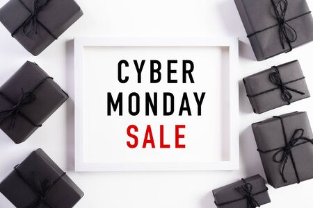 Top view of Cyber Monday Sale text on white picture frame with black gift box and Christmas ball and berries on white background. Shopping concept Boxing day and Cyber Monday composition.