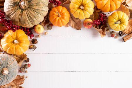 Draufsicht auf Herbstahornblätter mit Kürbis und roten Beeren auf weißem Holzhintergrund. Thanksgiving Day-Konzept.