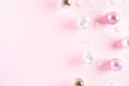 Christmas background concept. Top view of Christmas ball with snowflakes on light pink pastel background. Stock Photo
