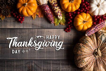 Draufsicht auf Herbstahornblätter mit Kürbis, Apfel, Mais und roten Beeren auf altem Holzhintergrund. Thanksgiving Day-Konzept.