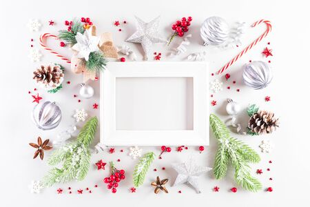 Christmas holidays composition Top view of white picture frame with gift box, Christmas tree decoration and red berries on white background with copy space for text. Stock Photo