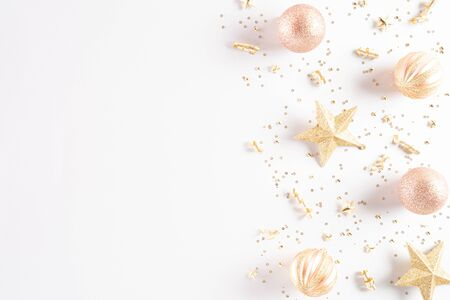 Christmas background concept. Top view of Christmas decoration, light golden and orange pastel  ball, star with snowflakes on white background.