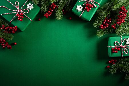 Christmas background concept. Top view of Christmas green gift box with decoration, spruce branches and red berries on green background.