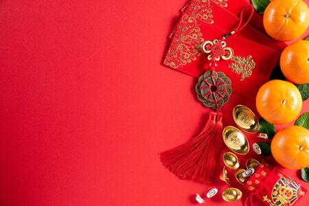 Chinesische Neujahrsfestdekorationen pow oder rotes Paket, orange und goldene Barren oder goldener Klumpen auf rotem Hintergrund. Chinesische Schriftzeichen FU in dem Artikel beziehen sich auf Glück, Glück, Reichtum, Geldfluss.