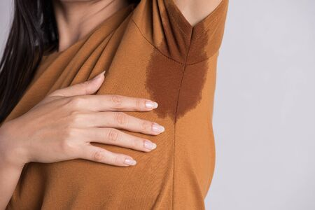 Close-up asian woman with hyperhidrosis sweating. Young asia woman with sweat stain on her clothes against grey background. Healthcare concept.