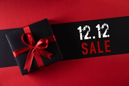 Online shopping of China, 12.12 singles day sale concept. Top view of black christmas boxes with red ribbon on black background with copy space for text 12.12 singles day sale.