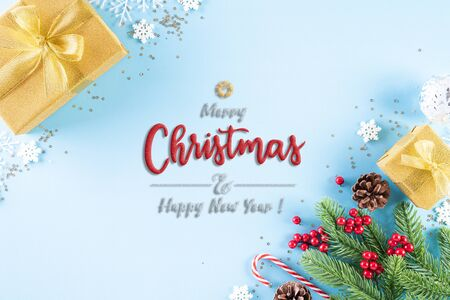Christmas background concept. Top view of Christmas golden gift box with candy cane decoration, spruce branches, star, red berries and bell on light blue pastel background.