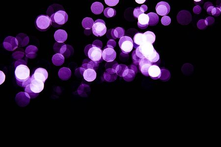 Abstract background purple bokeh with black background.