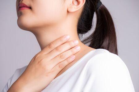 Halsschmerzen. Nahaufnahme der schönen jungen Frau Hand, die ihren kranken Hals berührt. Gesundheitswesen und medizinisches Konzept. Standard-Bild