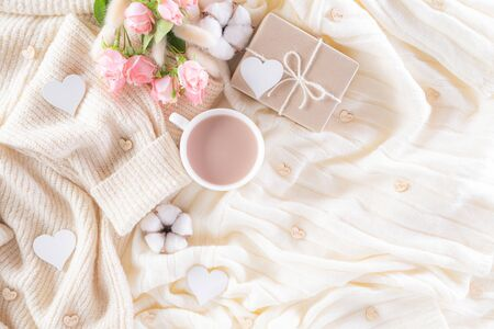 Pink paper hearts with gift box and roses, coffee cup on , beige sweater on cream colour knitted blanket and fluffy background. Love and Valentines day during Winter concept. Stok Fotoğraf
